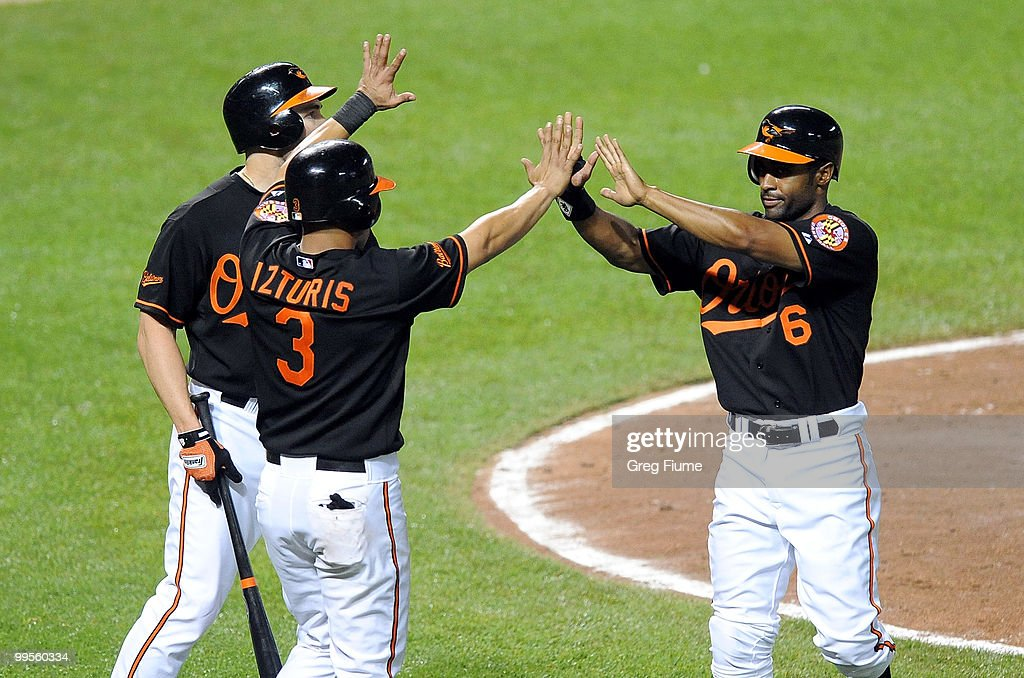 Corey Patterson #6 of the Baltimore Orioles celebrates with Luke Scott #30 and Cesar Izturis #3 after scoring in the sixth inning against the Cleveland Indians at Camden Yards on May 14, 2010 in Baltimore, Maryland.