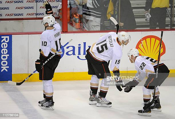 Corey Perry leaves the ice as Ryan Getzlaf gives a low five to Todd Marchant of the Anaheim Ducks after defeating the Nashville Predators 63 in Game...