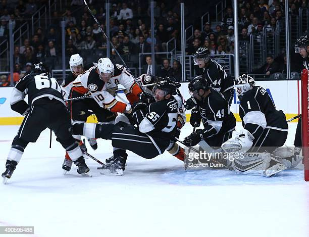 Corey Perry of the Anaheim Ducks and Jeff Schultz of the Los Angeles Kings battle for the puck in front of Kings goalie Jhonas Enroth during...