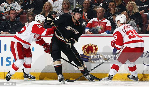 Corey Perry of the Anaheim Ducks battles for position against Jordin Tootoo and Cory Emmerton of the Detroit Red Wings in Game One of the Western...