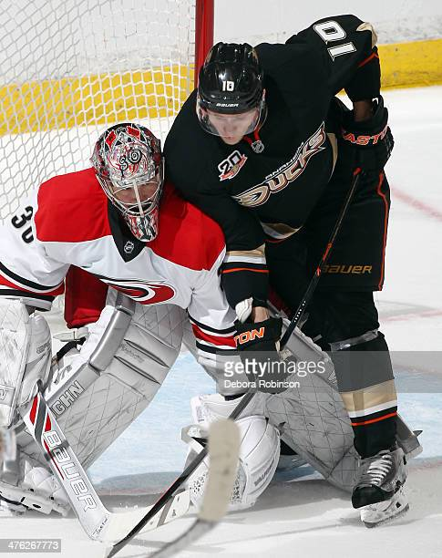 Corey Perry of the Anaheim Ducks battles for position in front of the net against Cam Ward of the Carolina Hurricanes on March 2 2014 at Honda Center...