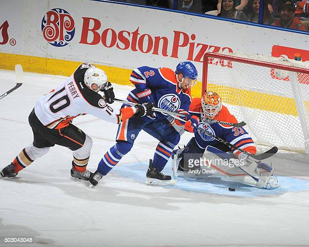 Corey Perry of the Anaheim Ducks battles for the puck against Andrej Sekera of the Edmonton Oilers on December 31 2015 at Rexall Place in Edmonton...