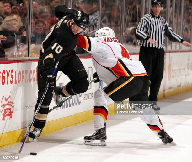 Corey Perry of the Anaheim Ducks defends the puck against Jim Vandermeer of the Calgary Flames at the Honda Center February 29 2008 in Anaheim...