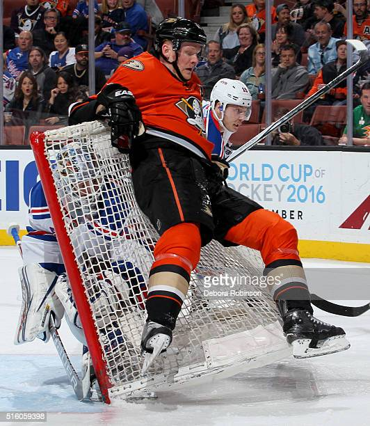 Corey Perry of the Anaheim Ducks falls back onto the net as Antti Raanta of the New York Rangers looks on from inside the net during the game on...
