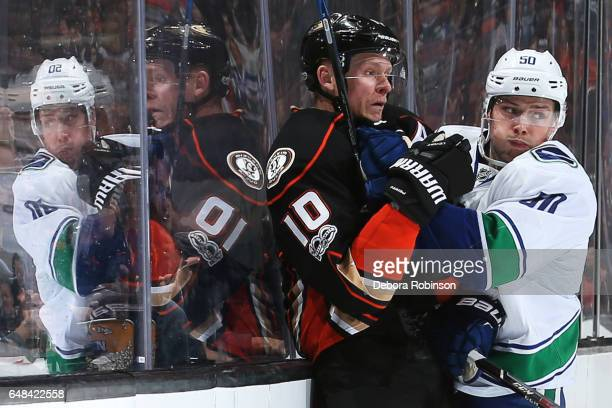 Corey Perry of the Anaheim Ducks gets checked by Brendan Gaunce of the Vancouver Canucks during the game on March 4 2017 at Honda Center in Anaheim...