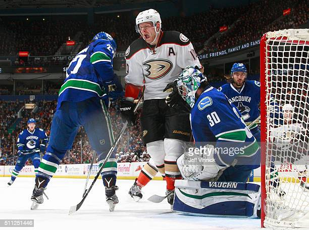 Corey Perry of the Anaheim Ducks reacts after getting hit by a shot between Ben Hutton and Ryan Miller of the Vancouver Canucks during their NHL game...