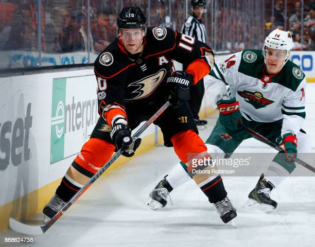 Corey Perry of the Anaheim Ducks skates with the puck with pressure from Joel Eriksson Ek of the Minnesota Wild during the game on December 8 2017 at...