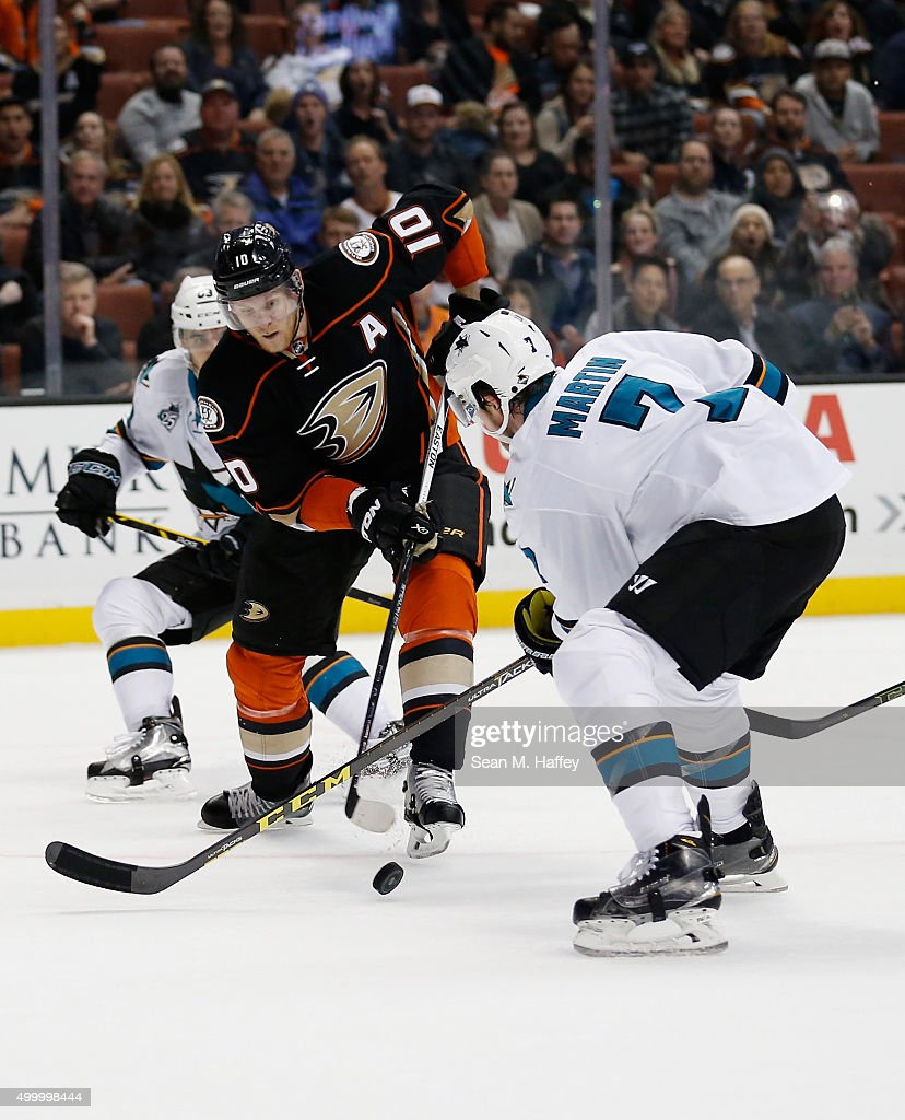 Corey Perry #10 of the Anaheim Ducks struggles to control a puck against Paul Martin #7 of the San Jose Sharks during the third period of a game at Honda Center on December 4, 2015 in Anaheim, California.