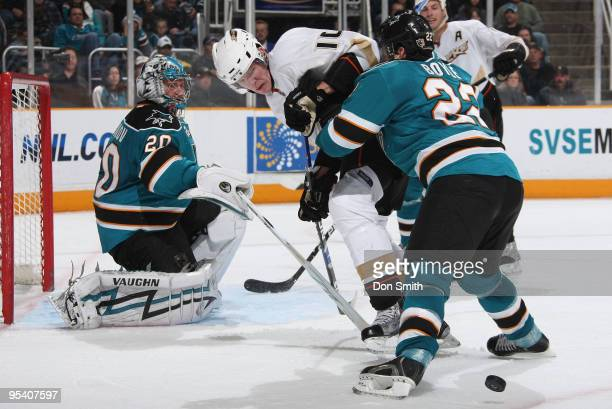 Corey Perry of the Anaheim Ducks tries to control the puck as Dan Boyle of the San Jose Sharks shoves him off and Evgeni Nabokov pokes it out of...