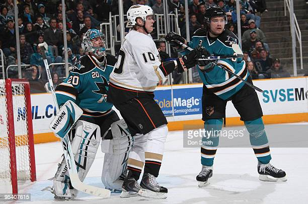 Corey Perry of the Anaheim Ducks tries to post up between Evgeni Nabokov and Douglas Murray of the San Jose Sharks during an NHL game on December 26,...