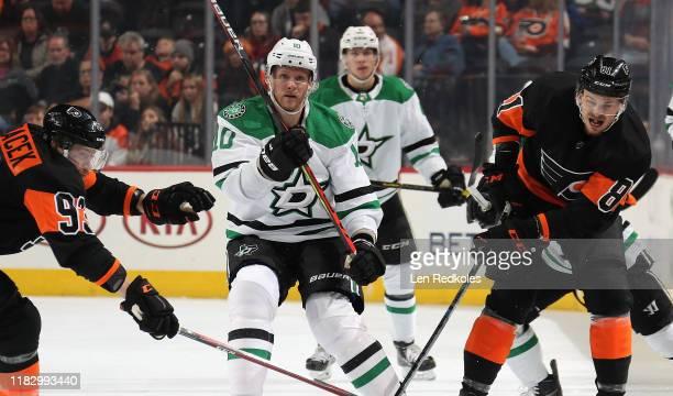 Corey Perry of the Dallas Stars skates between against Jakub Voracek and Carsen Twarynski of the Philadelphia Flyers on October 19, 2019 at the Wells...