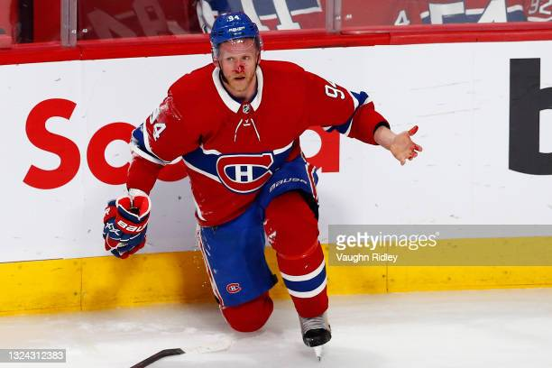 Corey Perry of the Montreal Canadiens reacts after his face is cut with a stick against the Vegas Golden Knights during the first overtime period in...