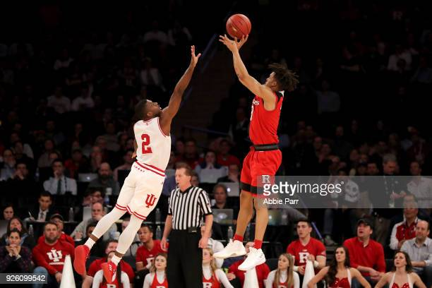 Corey Sanders of the Rutgers Scarlet Knights takes a shot against Josh Newkirk of the Indiana Hoosiers in the second half during the second round of...