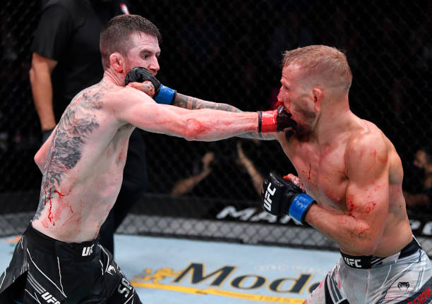 Corey Sandhagen and T.J. Dillashaw trade punches in their bantamweight fight during the UFC Fight Night event at UFC APEX on July 24, 2021 in Las...