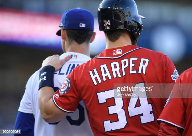 Corey Seager of the Los Angeles Dodgers and Bryce Harper of the Washington Nationals meet on first base in the third inning at Dodger Stadium on...