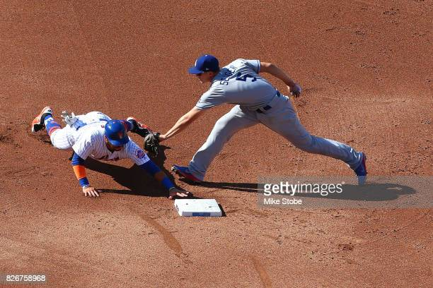 Corey Seager of the Los Angeles Dodgers applies the tag late as Rene Rivera of the New York Mets slides into second safley in the second inning at...