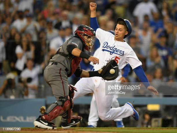 Corey Seager of the Los Angeles Dodgers beats the throw to Alex Avila of the Arizona Diamondbacks to score in the third inning at Dodger Stadium on...