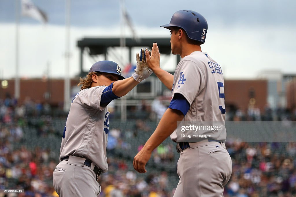 Corey Seager #5 of the Los Angeles Dodgers celebrates with Enrique Hernandez #14 after scoring on a ground out by Adrian Gonzalez #23 of the Los Angeles Dodgers off of Tyler Chatwood #32 of the Colorado Rockies to take a 1-0 lead in the first inning at Coors Field on April 23, 2016 in Denver, Colorado
