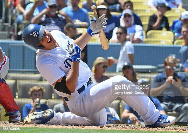 Corey Seager of the Los Angeles Dodgers goes down after is hit on the right hand from a pitch thrown by Elvis Araujo of the Philadelphia Phillies in...