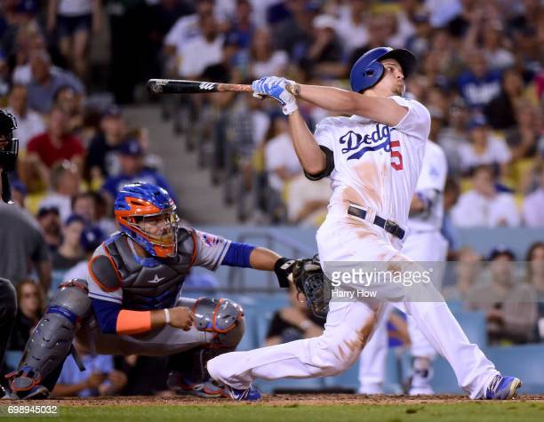 Corey Seager of the Los Angeles Dodgers hits a three run homerun in front of Rene Rivera of the New York Mets for his third homerun of the game to...
