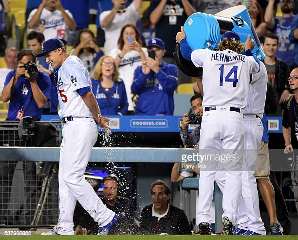 Corey Seager of the Los Angeles Dodgers reacts to a dousing of water from Enrique Hernandez and Scott Van Slyke to celebrate a three homerun night...