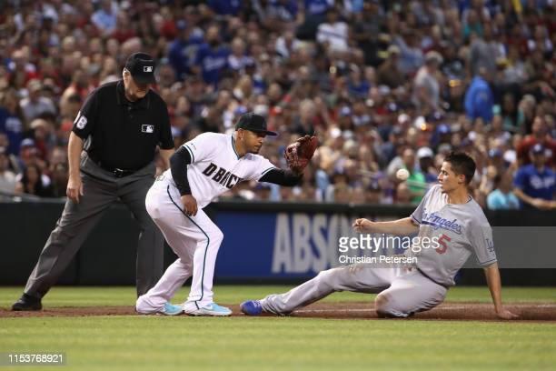 Corey Seager of the Los Angeles Dodgers safely slides into third base ahead of infielder Eduardo Escobar of the Arizona Diamondbacks during the third...