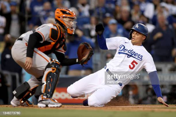 Corey Seager of the Los Angeles Dodgers scores against Buster Posey of the San Francisco Giants on a double by Trea Turner during the first inning in...