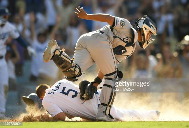 Corey Seager of the Los Angeles Dodgers slides past Francisco Mejia of the San Diego Padres for the winning run after being driven in by Max Muncy at...