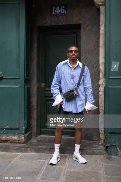 Corey Stokes is seen on the street attending Men's Paris Fashion Week wearing blue/white shirt black crossbody bag black biker shorts white Nike...