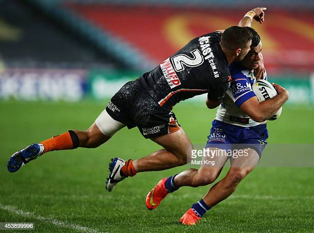 Corey Thompson of the Bulldogs is tackled by Jy Hitchcox of the Tigers during the round 24 NRL match between the Canterbury Bulldogs and the Wests...