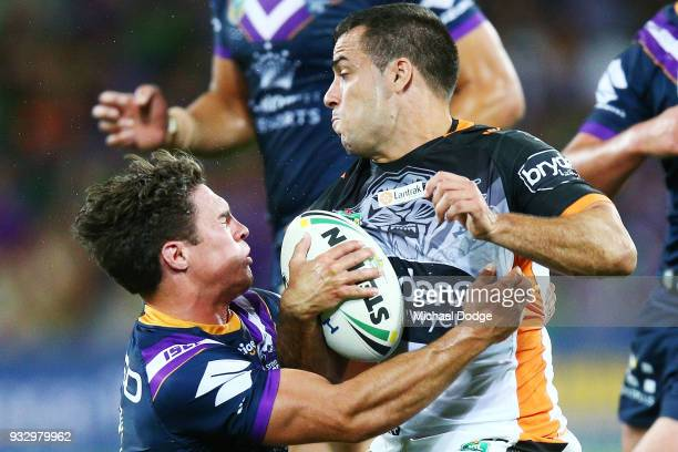 Corey Thompson of the Tigers is tackled by Brodie Croft of the Storm during the round two NRL match between the Melbourne Storm and the Wests Tigers...