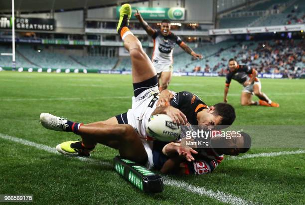 Corey Thompson of the Tigers is tackled over the line in the corner by Daniel Tupou of the Roosters in the final minutes during the round 13 NRL...