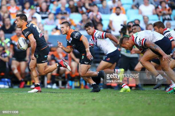 Corey Thompson of the Tigers makes a break during the round one NRL match between the Wests Tigers and the Sydney Roosters at ANZ Stadium on March 10...