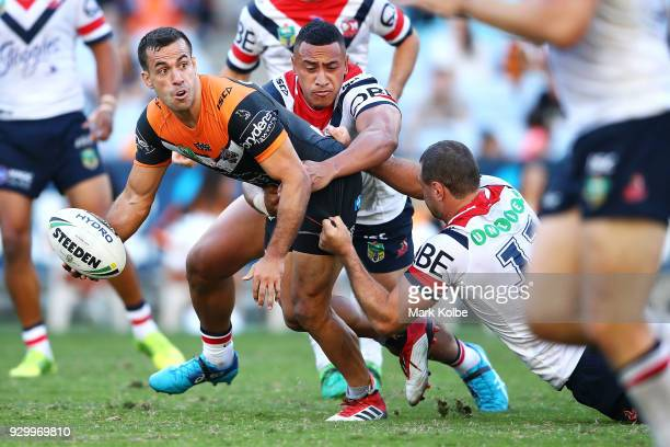 Corey Thompson of the Tigers passes as he is tackled during the round one NRL match between the Wests Tigers and the Sydney Roosters at ANZ Stadium...