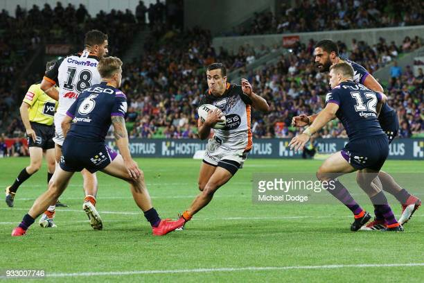 Corey Thompson of the Tigers runs with the ball between Cameron Munster and Ryan Hoffman of the Storm during the round two NRL match between the...