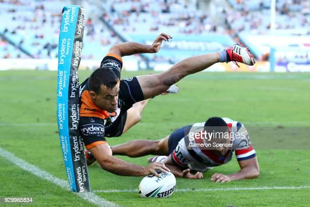 Corey Thompson of the Tigers scores a try during the round one NRL match between the Wests Tigers and the Sydney Roosters at ANZ Stadium on March 10...