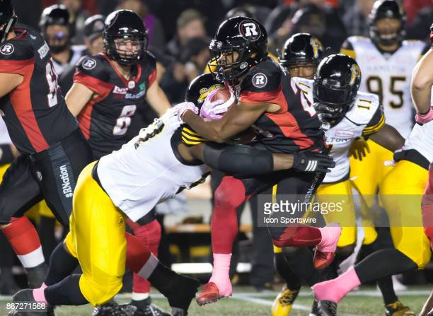 Corey Tindal of the Ottawa Redblacks gets tackled by the Hamilton TigerCats in Canadian Football League play at TD Place Stadium in Ottawa Canada The...