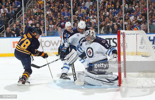 Corey Tropp of the Buffalo Sabres scores his first NHL goal against Dustin Byfuglien and Ondrej Pavelec of the Winnipeg Jets at First Niagara Center...