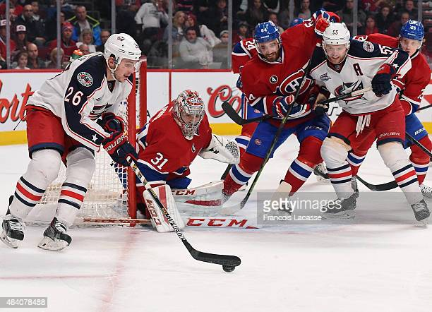 Corey Tropp of the Columbus Blue Jackets carries the puck near goaltender Carey Price of the Montreal Canadiens while Mark Letestu defends the goal...