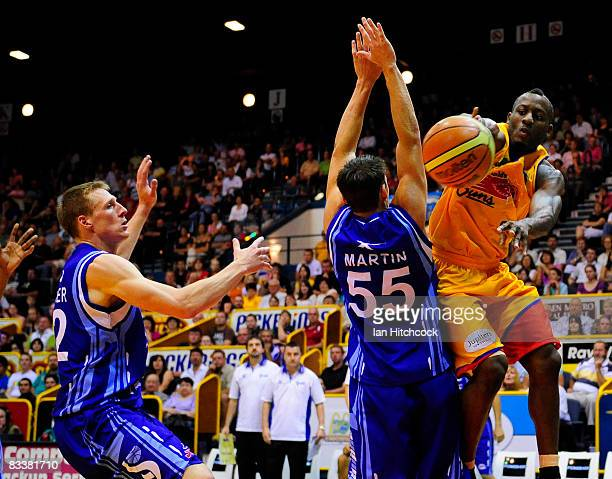 Corey Wiliams of the Crocodiles passes the ball past Damian Martin and David Gruber of the Spirit during the round six NBL match between the...