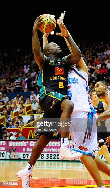 Corey Williams of the Crocodiles makes a layup over Craig Bradshaw of the Blaze during the round 15 NBL match between the Townsville Crocodiles and...