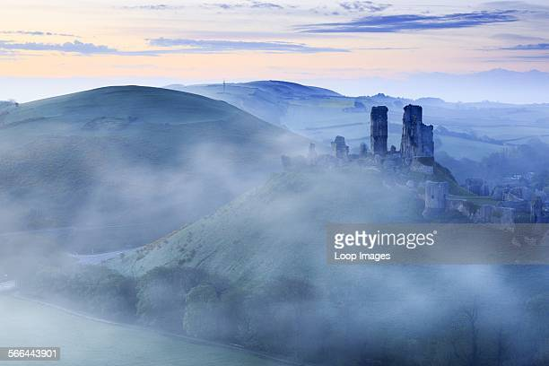 Corfe Castle in Dorset rising above early morning mist