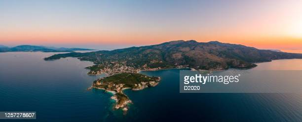 corfu, kerkyra, aerial panoramic photo of the town and port of cassiopeia / kassiopia at summer dusk - corfu stock pictures, royalty-free photos & images