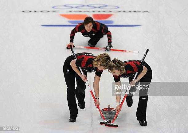 Cori Bartel and Carolyn Darbyshire of Canada brush the ice as skip Cheryl Bernard looks on during the women's curling semifinal game between Canada...