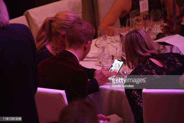 Corinna Schumacher Mick Schumacher and Sabine Kehm look into the mobile phone where Gina Schumacher is shown during the German Sports Media Ball at...