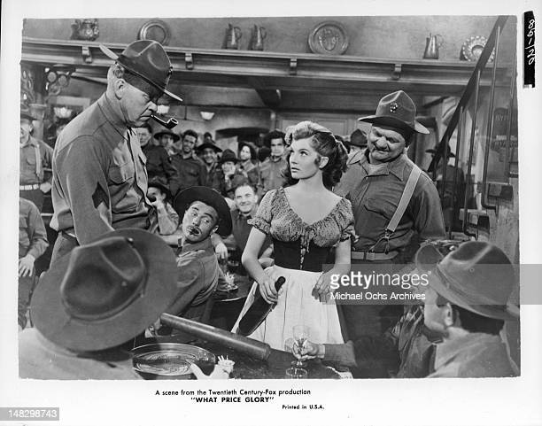 Corinne Calvet is the center of attention in a room filled with men in a scene from the film 'What Price Glory' 1952
