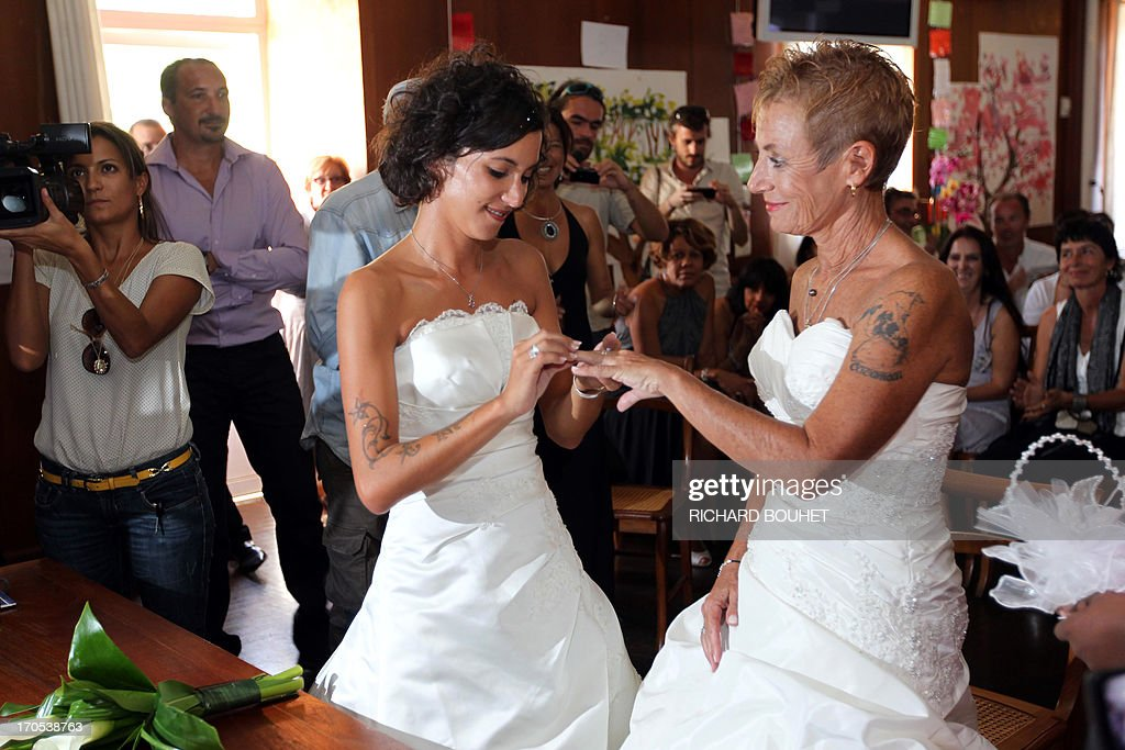 Corinne Denis (R) and Laurence Cerveaux (L) exchange rings as part of their wedding ceremony at Saint-Paul de la Reunion city hall during the first official gay marriage French island of La Reunion. France is the 14th country to legalise same-sex marriage, an issue that has also divided opinion in many other nations. The definitive vote in the French parliament came on April 23 when the law was passed legalising both homosexual marriages and adoptions by gay couples.