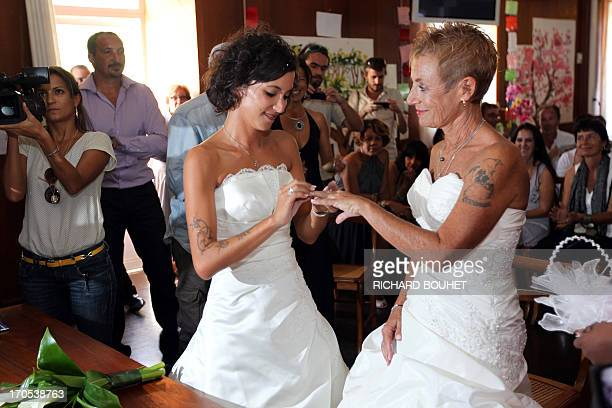 Corinne Denis and Laurence Cerveaux exchange rings as part of their wedding ceremony at SaintPaul de la Reunion city hall during the first official...