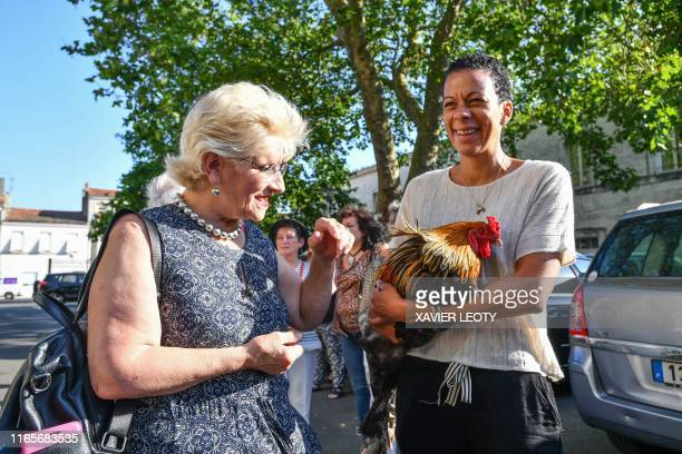 Corinne Fesseau stands next to her rooster Maurice held by a member of its support committee as she arrives in Rochefort western France on July 4...
