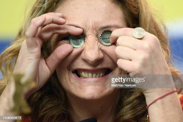 Corinne Masiero puts bottle caps in her eyes at the Delete History press conference during the 70th Berlinale International Film Festival Berlin at...